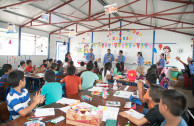 Members of the OSEMAP giving the children an invitation to the concert held at the shelter of the La Industria farm, Escuintla.